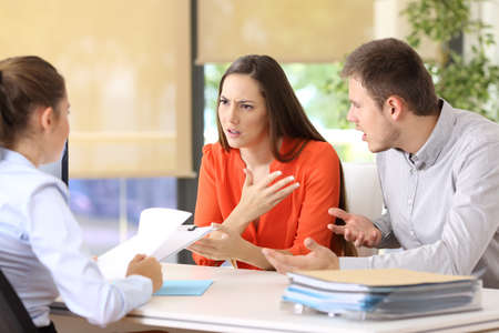 Angry couple arguing telling their problems sitting in a desktop of a marriage counseling or office Archivio Fotografico