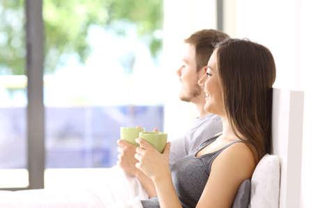 屋外背景が緑色のアパートのベッドの上に座っている寝室の外探しているカップルの側面図