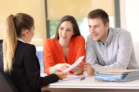 Two happy customers solving doubts about a contract with the saleswoman at office