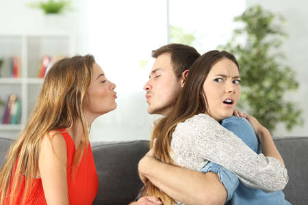 Girlfriend discovering that her boyfriend is cheating with her best friend at home Stockfoto