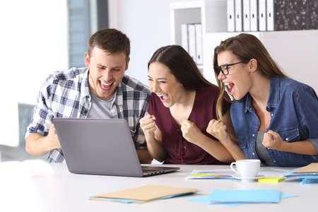 Drie opgewonden medewerkers lezen goed nieuws online in een laptop op een bureau op kantoor