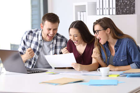 사무실에서 책상에 앉아 좋은 결과 보고서를 읽는 세 흥분된 노동자