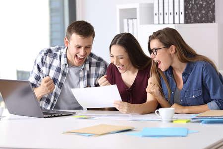 3 興奮労働者オフィスでデスクトップに座って良い結果報告書を読む