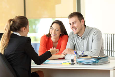 Happy couple being attended by office worker at office Stockfoto