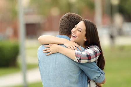 Gelukkige ontmoeting van twee vrienden die buiten in een park knuffelen