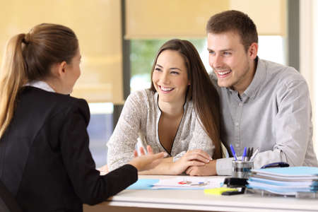 Gelukkig paar dat met een makelaar in onroerend goed op kantoor spreekt
