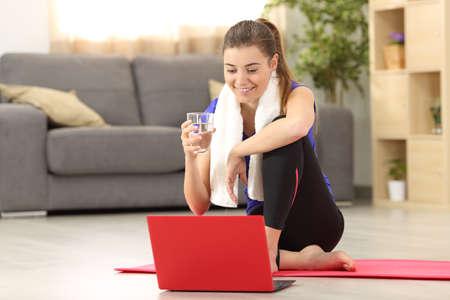 Vista frontale di una donna di forma fisica che tiene un bicchiere d'acqua che guarda in linea esercitazioni che si siedono sul pavimento nel salone a casa Archivio Fotografico - 82090887
