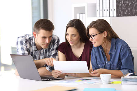 Three coworkers working at office comparing data with laptop and documents Stock Photo