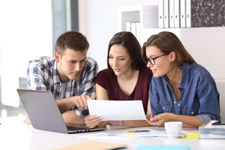 Tre colleghi che lavorano in ufficio confrontando i dati con il computer portatile e documenti