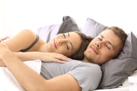 Happy couple sleeping together lying on a bed of an hotel room or home