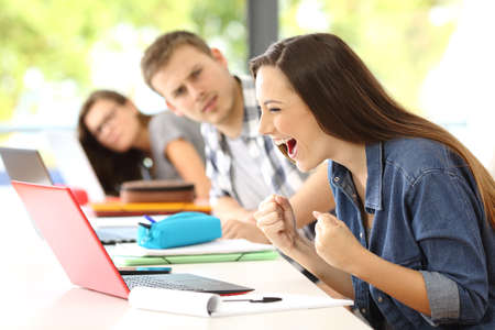 Excited student receiving good news on line in a classroom with her surprised classmates looking Stock Photo
