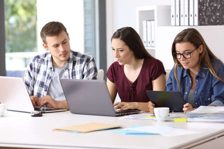 Three attentive employees working on line together with multiple devices at office Stock Photo