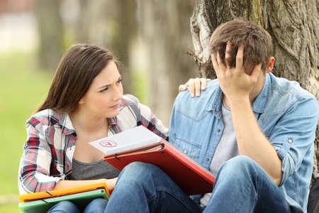 Vriend troostend aan een verdrietige student met mislukte examen op het gras in een park zitten