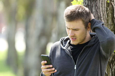 Confused single teen reading a message in a smart phone outdoors in a park Foto de archivo