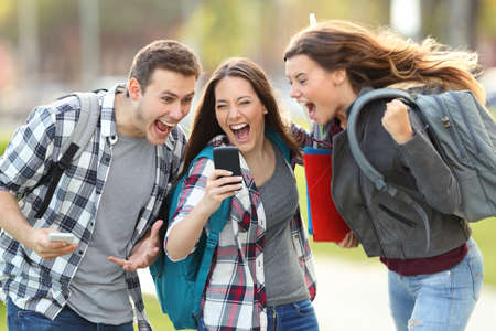 Front view of three excited students receiving good news on line in a mobile phone in an university campus or street Archivio Fotografico