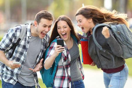 Vooraanzicht van drie opgewonden studenten die goed nieuws online ontvangen in een mobiele telefoon op een universitaire campus of straat
