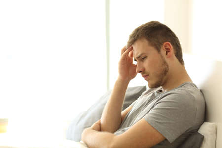 Triste soltero lamentándose sentado en la cama en la cama de una habitación de hotel o casa Foto de archivo - 83043321