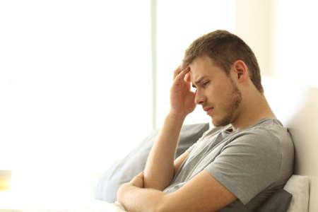 Verdrietige alleenstaande man treurt zittend op het bed op het bed van een hotelkamer of thuis