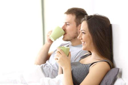 ホテルの部屋や自宅のベッドの上のカップを保持している朝食を持っているリラックスしたカップルの側面図 写真素材