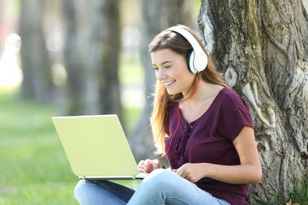 Single teen listening and watching media content on line with headphones and a laptop Stock fotó