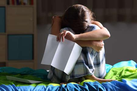 Vue de face d'un seul adolescent triste se lamentant assis sur son lit après avoir lu une lettre avec une lumière sombre en arrière-plan Banque d'images - 83043398