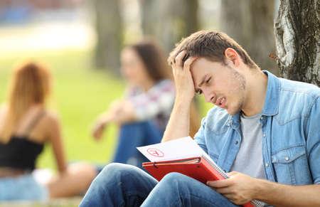 Único estudiante triste comprobar un examen fallido sentado en la hierba en un parque con la gente desenfocada en el fondo