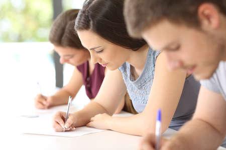 Sluit omhoog van drie geconcentreerde studenten die een examen in een klaslokaal doen