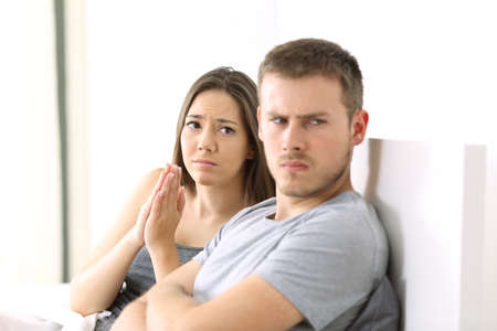 breaking: Wife begging to her angry husband sitting on the bed in a house interior