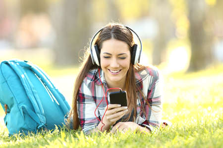 Happy student listening audio lessons on line with headphones and a smart phone lying on the grass in a campus