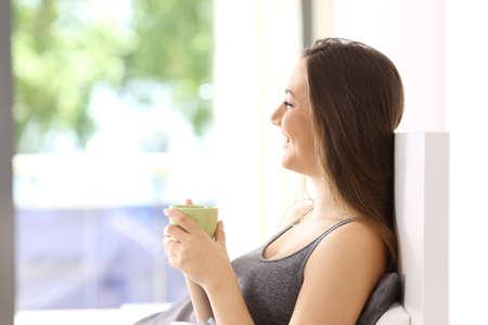 ホテルの部屋やアパートのベッドで朝食をとり、幸せな独身女性の側面図 写真素材