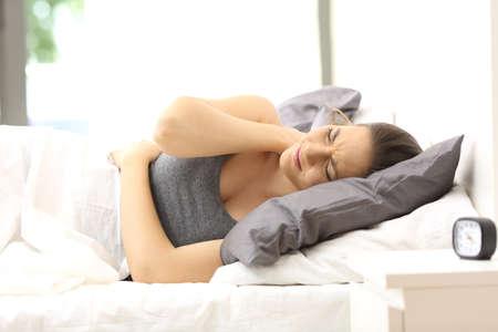Eenzame vrouw lijdt nekpijn na een slechte nacht in een ongemakkelijk bed van een hotelkamer of thuis