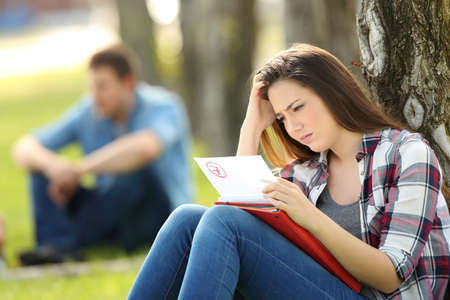 Single sad student looking at failed exam sitting on the grass in a park with unfocused people in the background Stock Photo