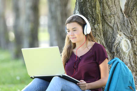 Single teen girl studying watching video tutorials on line in a laptop sitting on the grass leaning in a tree in a park