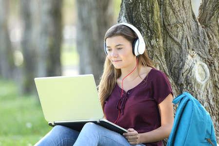 Single Teen Mädchen studieren Video-Tutorials online in einem Laptop sitzen auf dem Rasen in einem Baum in einem Park gelehnt Standard-Bild - 83983350