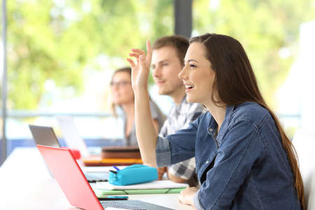 Side view of a student raising arm sitting in a classroom with classmates in the background