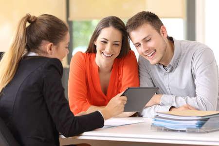 Vendedor mostrando productos en línea con una tableta a los clientes en una computadora de escritorio en la oficina