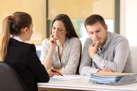 Office worker attending and showing contract trying to convince to a suspicious couple sitting in a desk at office Foto de archivo
