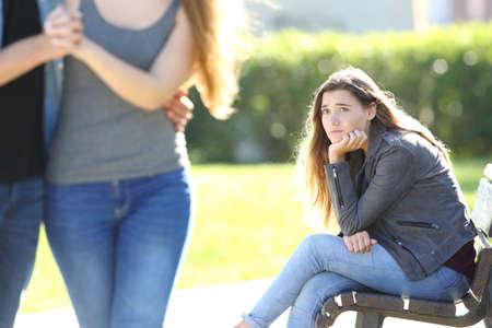 Droevige eenzame meid die een liefdespaar ziet die buiten in een park loopt Stockfoto