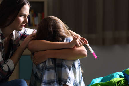 Sister comforting to a pregnant sad teen in her bedroom with a dark light in the background Stock Photo