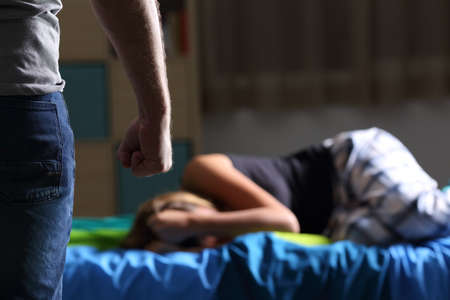 Victime de maltraitance allongée sur le lit de sa chambre à coucher et poing agresseur au premier plan avec une lumière sombre en arrière-plan