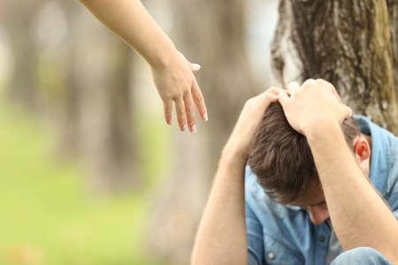 Droevige tiener zit op het gras in een park en een vrouwelijke hand die hulp biedt met een groene achtergrond