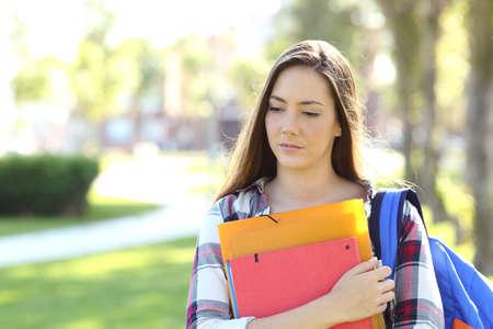 야외 공원에서 폴더를 들고 거리에서 걷고 슬픈 학생의 전면보기 초상화