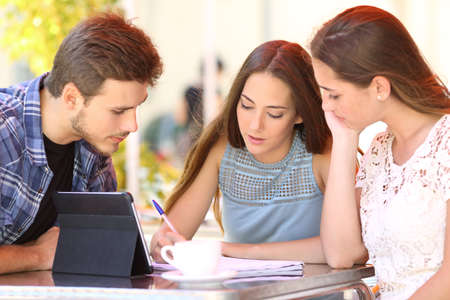 investigando: Tres estudiantes concentrados trabajando juntos en línea y tomando notas sentado en la mesa en una terraza del restaurante Foto de archivo