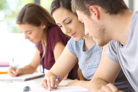 Student helpen bij een klasgenoot in klaslokaal met een ander meisje op de achtergrond Stockfoto