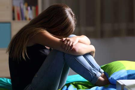 Retrato de un solo adolescente triste sentado en la cama en su dormitorio con una luz oscura en el fondo Foto de archivo - 82231661