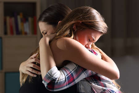 Side view of two sad good friends embracing in a bedroom in a house interior with a dark light in the background Standard-Bild