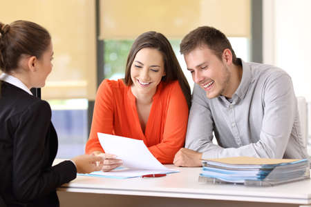 Saleswoman talking with a couple of happy customers sitting in a desktop at office Stock Photo