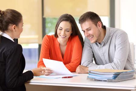 Verkäuferin spricht mit ein paar glückliche Kunden sitzen in einem Desktop im Büro Standard-Bild