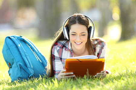 e book device: Front view portrait of a student reading notes and listening an audio tutorial on line lying on the grass in a park
