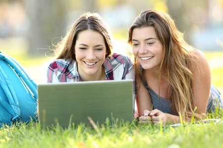 線、公園の草の上に横たわるラップトップでコンテンツを見て 2 つの幸せな学生の正面図